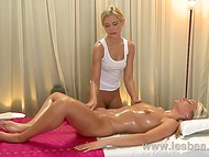 Adorable masseuse slowly moves her hands to the beautiful shaved pussy of her young patient